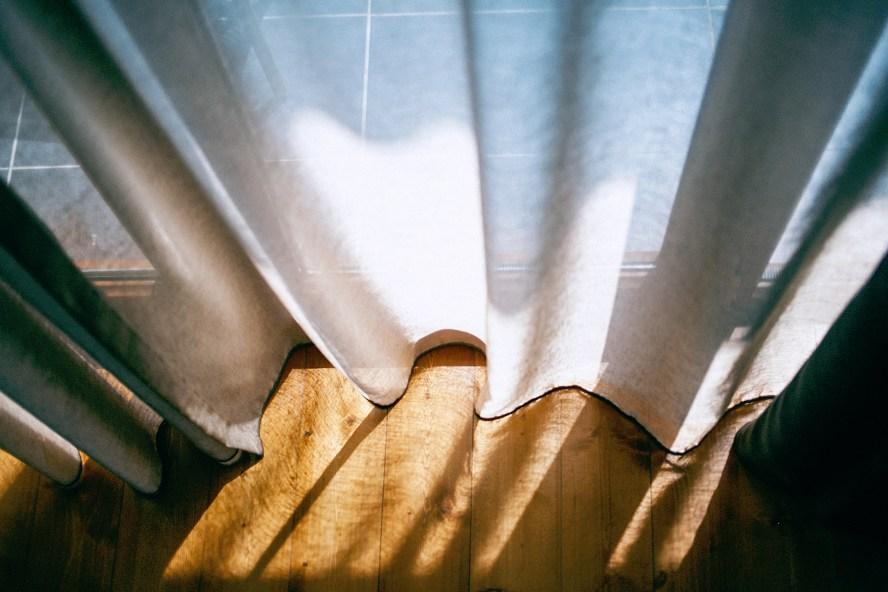 przed oknem w świetle zasłony